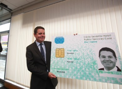 Paschal Donohoe holds up a mock-up of a PSC after he registered for one. August, 2016.