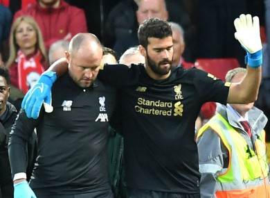 Alisson is helped off the pitch.