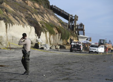 A San Diego County Sheriff's deputy looks on as search and rescue personnel work at the site of a cliff collapse at a popular beach.