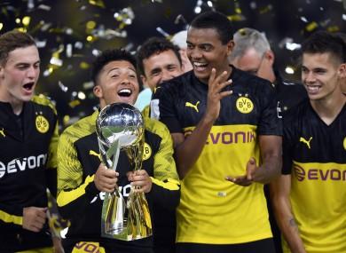 Jadon Sancho celebrates with the trophy.