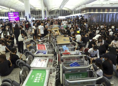 Protesters used luggage trolleys to block the walkway to the departure gates yesterday.