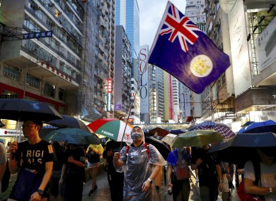 A protester waves a Hong Kong colonial-era flag as others march along a street in Hong Kong on Sunday.