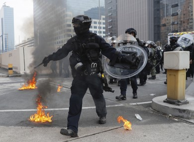 Riot police move small fires during a protest in Hong Kong today