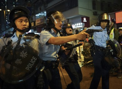 Policemen draw their guns during a confrontation with demonstrators during in Hong Kong last weekend