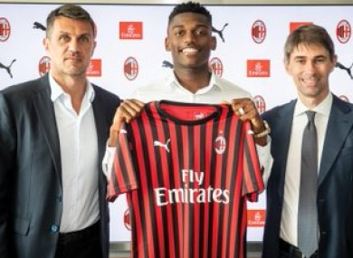 Leao holding up the jersey with (left) technical director Paolo Maldini.