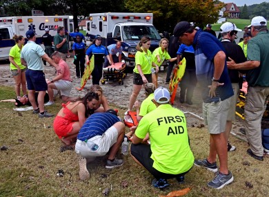 Fans are assisted by medical personnel after a lightning strike at the golf course in Atlanta