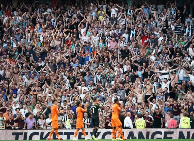 Newcastle fans celebrate with the players at full-time.