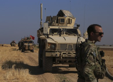 Turkish and American armoured vehicles patrol as they conduct joint ground patrols in the so-called 'safe zone' on the Syrian side of the border with Turkey