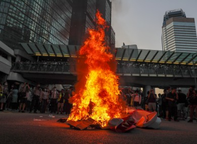 Protesters burn a China 70th anniversary celebration banner in Hong Kong last night.