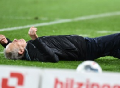 Christian Streich lies prone on the touchline after being barged over.
