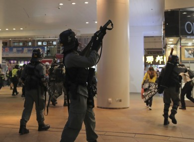 Police in Hong Kong point guns at protesters in a shopping centre.