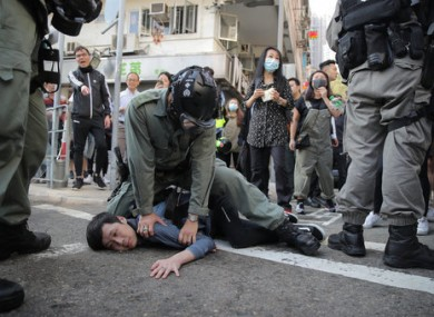 A protester is detained by police in Hong Kong.