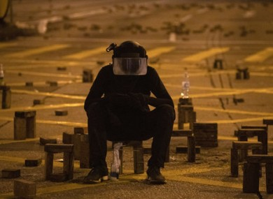 A protester sits with brick obstacles and Molotov cocktail on a barricade road near the Hong Kong Polytechnic University.