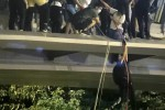 Protestors use a rope to lower themselves from a pedestrian bridge to waiting motorbikes in order to escape from Hong Kong Polytechnic University.