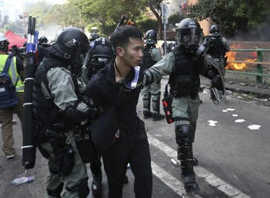 Riot police detain a protester yesterday.