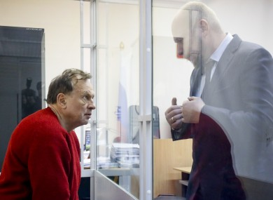 Oleg Sokolov listens to his lawyer sitting in a cage waiting for a court session in St. Petersburg.