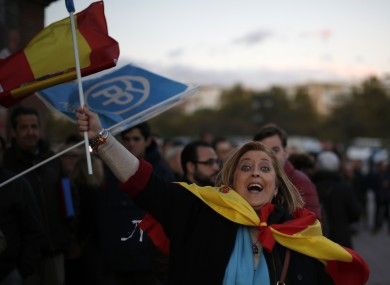 A woman waves a Spanish flag at a Popular Party campaign event.