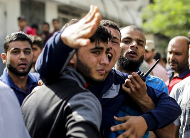 Palestinian men mourn outside the al-Shifa hospital in Gaza city.