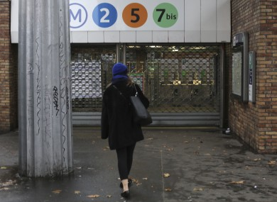 A woman arrives at a closed subway station in Paris.