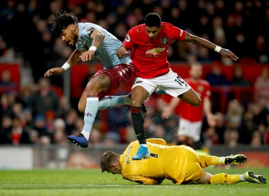 Aston Villa goalkeeper Tom Heaton and Aston Villa's Tyrone Mings (left) battle for the ball with Manchester United's Marcus Rashford.
