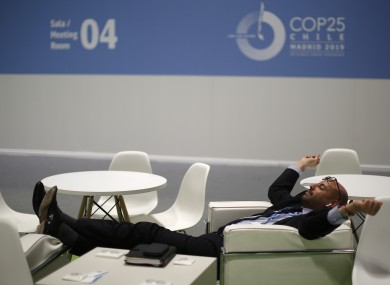 A visitor rests at the COP25 climate talks congress in Madrid