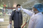 A Chinese medical worker checks the body temperature of a passenger for prevention of the new coronavirus and pneumonia at Chengdu Shuangliu International Airport