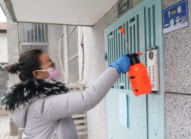 Women disinfects the door of a complex in Wuhan.