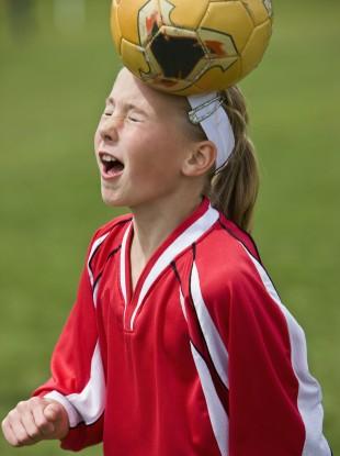 A young female footballer heading a ball.