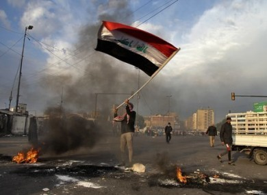 A protester in Iraq waves the national flag during a demonstration against the Iranian missile strike.