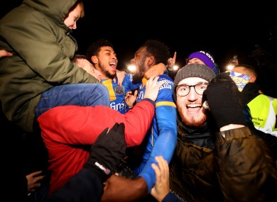 Shrewsbury Town's Aaron Pierre (centre) celebrates victory after the final whistle with team-mate Josh Laurent (left) and fans.
