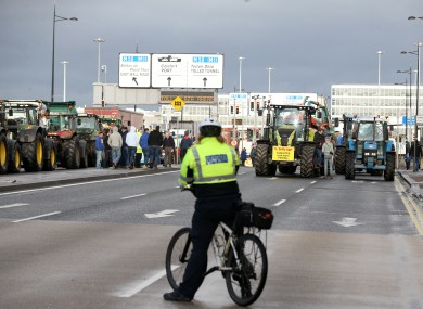 Gardaí watch as a line of tractors are stuck at Dublin Port during their January protest.