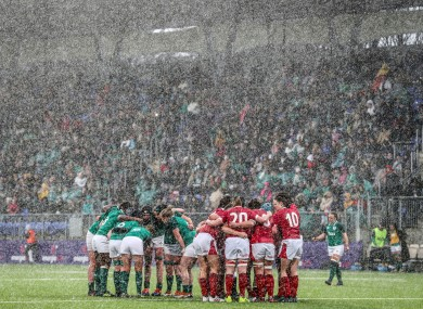 The Ireland and Wales teams huddle as the rain pours down during the game.