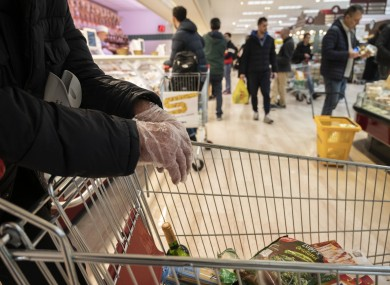 File photo. A man wearing protective gloves in an Italian supermarket