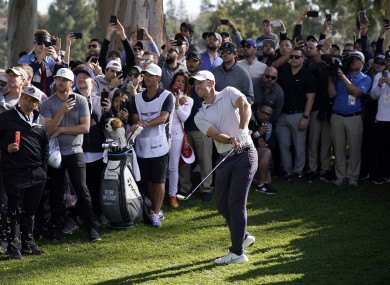 Rory McIlroy watches his second shot while surrounded by spectators on the 18th hole during the third round of the Genesis Invitational golf tournament at Riviera.