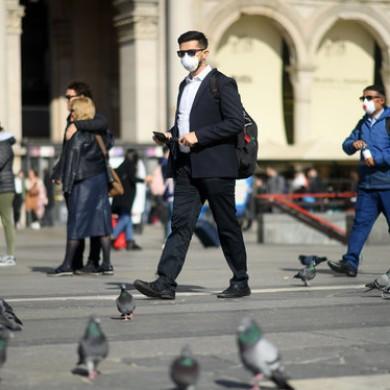 People wear masks as they walk in Milan.