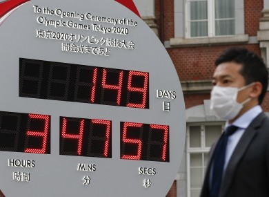 A man wearing a surgical mask walks past a big Omega One-Year Countdown clock for the opening ceremony of the Tokyo 2020 Olympic and Paralympic Games outside Tokyo Station.