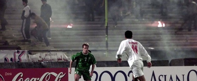 Jason McAteer plays on as the stands are lit on fire by lranian fans.