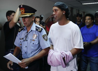 Ronaldinho being escorted by police officers in Paraguay.