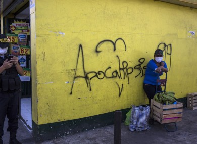 A woman waits with her purchases next to a wall spray painted with the word 'Apocalypse' in Spanish. Lima, Peru.