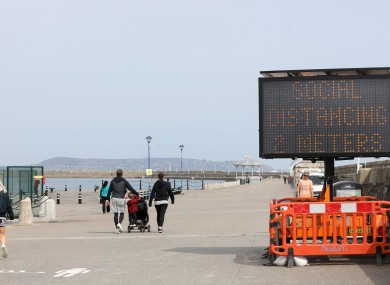 People walking on a sunny Dun Laoghaire pier last week reminded of social distancing.