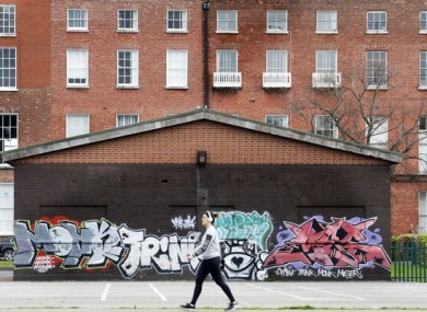 A woman walks through Mountjoy Square.