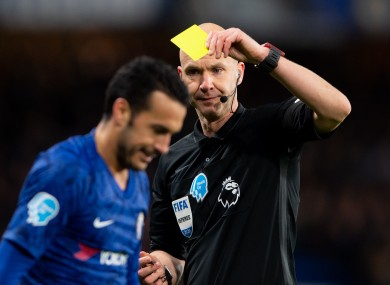 Referee Anthony Taylor booking Chelsea's Pedro during a Premier League game against Man United in February.