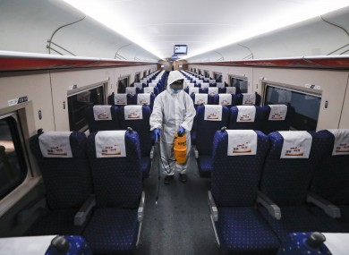 A staff member disinfects the interior of a train at a depot in Wuhan, China yesterday in preparation for today.