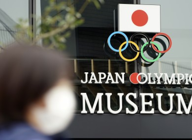 A woman wearing a mask against the spread of Covid-19 walks in front of the Japan Olympic Museum building in Tokyo.