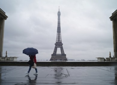A woman walks on the deserted Trocadero square today in front of the Eiffel Tower during nationwide confinement measures to counter Covid-19.