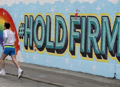 A man runs past a new mural in Dublin's city centre inspired by the new HSE 'Hold Firm' campaign - which took its inspiration from a poem by President of Ireland Michael D Higgins.