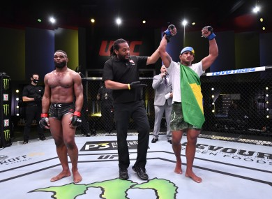 Gilbert Burns is announced the winner alongside referee Herb Dean and opponent Tyron Woodley.