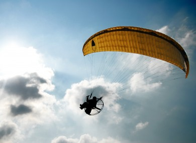 A powered paraglider pilot in flight with a blue cloudy sky. (File)