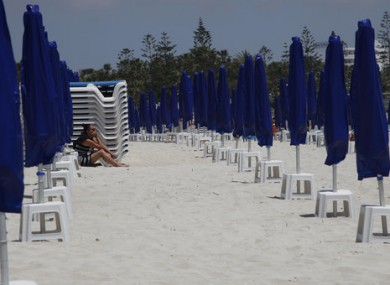 A woman sits on an empty beach in Ayia Napa.