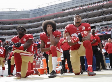 Colin Kaepernick takes a knee with Eli Harold (left) and Eric Reid (right) in 2016.